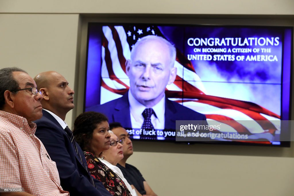 Newly naturalized citizens watch a video presentation featuring United States Secretary of Homeland Security John Kelly during a naturalization ceremony on June 19, 2017 in San Francisco, California. 29 former refugees from 17 different countries were sworn in as Americaan citizens during a ceremony to mark World Refugee Day. World Refugee Day is Tuesday, June 20.