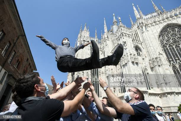 Newly ordered Catholic priest opens his arms as he is launched in the air by friends and family outside the Duomo Cathedral, in Milan, on June 12,...