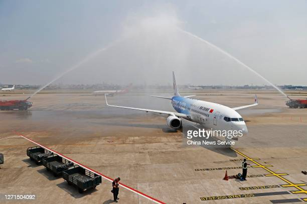 A newly painted Boeing 737 aircraft of Air China with patterns of the emblems and mascots of Beijing 2022 Winter Olympics passes through the water...