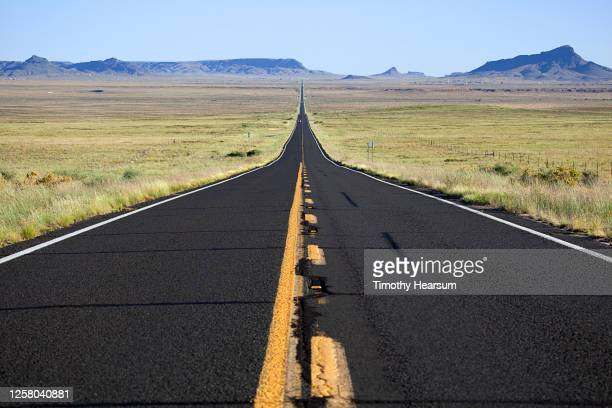 newly paved road leads straight to the horizon; mountains, mesas and blue sky beyond - timothy hearsum fotografías e imágenes de stock