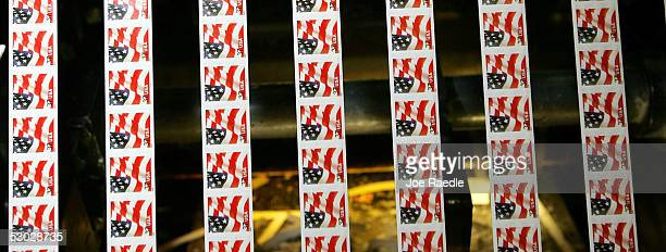 Newly printed sheets of stamps run off the presses at the United States Treasury Bureau of Engraving and Printing facility June 2 2005 in Washington...