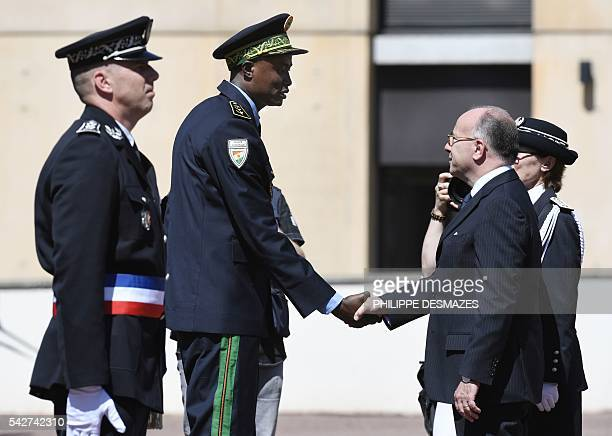 Newly promoted Nigeria's first ranked of foreign police chief shakes hand with French Interior minister Bernard Cazeneuve next to school director...