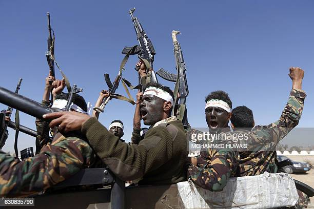 Newly recruited Houthi fighters chant slogans as they ride a military vehicle during a gathering in the capital Sanaa to mobilize more fighters to...