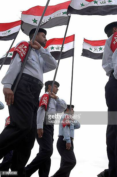 Newly recruited Iraqi security men parade holding Iraqi national flags during their graduation ceremony at alZubair Police Academy in southern Iraq...