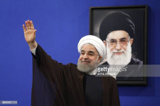 Newly reelected Iranian President Hassan Rouhani gestures after delivering a televised speech in the capital Tehran on May 20 2017 A portrait of...