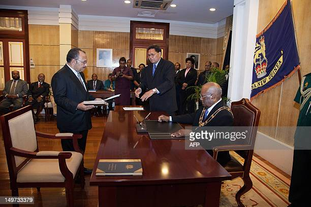 Newly reelected Papua New Guinea Prime Minister Peter O'Neill holds a bible as he is sworn in by Governor General Michael Ogio in Port Moresby on...