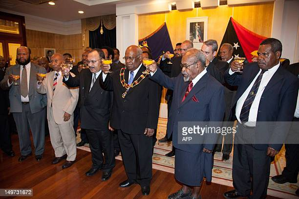 Newly reelected Papua New Guinea Prime Minister Peter O'Neill raises a toast with his cabinet in Port Moresby on August 3 2012 O'Neill was reelected...