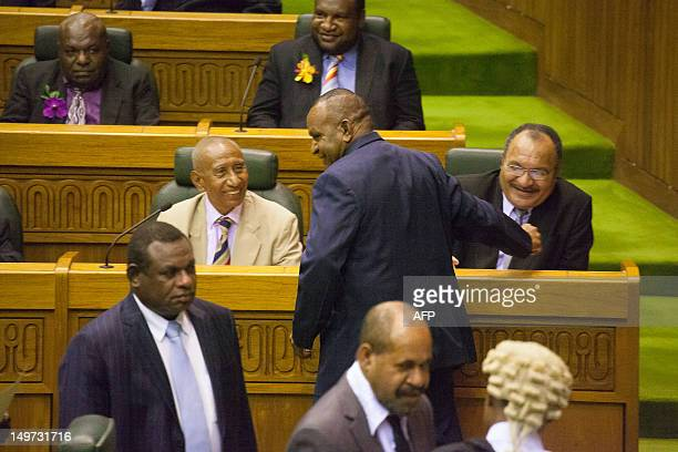 Newly reelected Papua New Guinea Prime Minister Peter O'Neill shakes hands with Belden Namah as Sir Julius Chan smiles in Port Moresby on August 3...