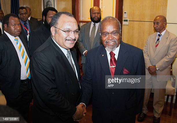 Newly reelected Papua New Guinea Prime Minister Peter O'Neill shakes hands with former prime minister Sir Michael Somare in Port Moresby on August 3...