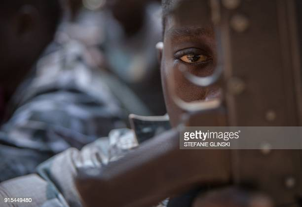 TOPSHOT A newly released child soldier looks through a rifle trigger guard during a release ceremony for child soldiers in Yambio South Sudan on...
