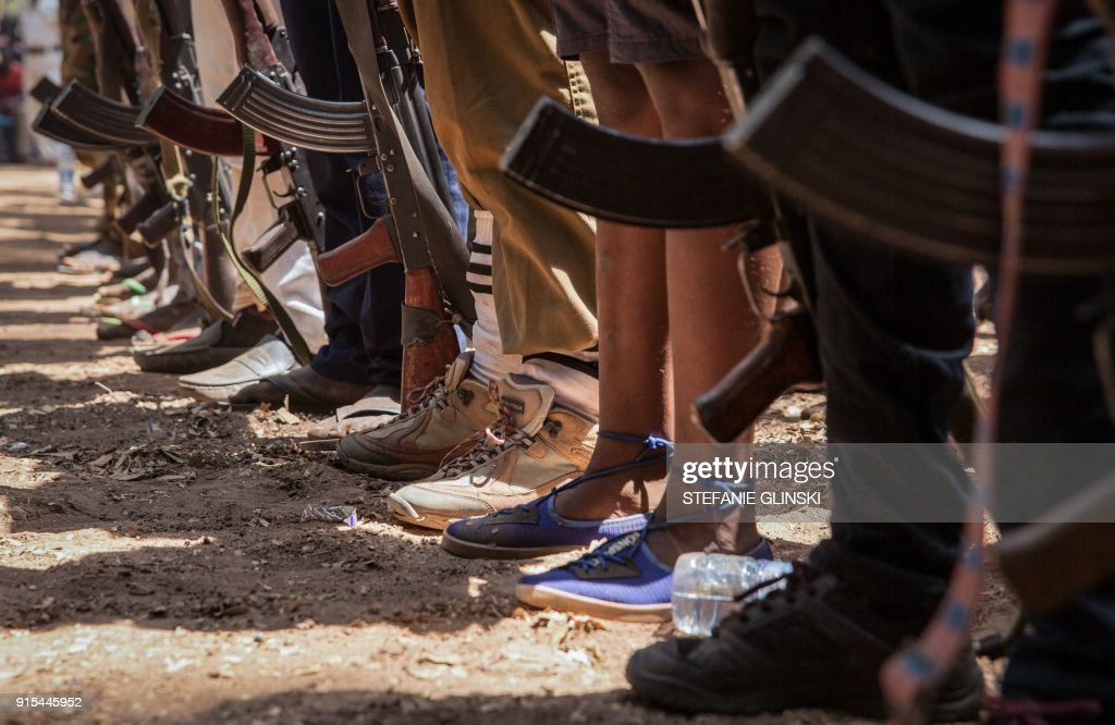 TOPSHOT - Newly released child soldiers stand with rifles during their release ceremony in Yambio, South Sudan, on February 7, 2018. More than 300 child soldiers, including 87 girls, have been released in South Sudan's war-torn region of Yambio under a programme to help reintegrate them into society, the UN said on on Februar y 7, 2018. A conflict erupted in South Sudan little more than two years after gained independence from Sudan in 2011, causing tens of thousands of deaths and uprooting nearly four million people. The integration programme in Yambio, which is located in the south of the country, aims at helping 700 child soldiers return to normal life. / AFP PHOTO / Stefanie Glinski