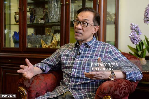 Newly released Malaysian politician Anwar Ibrahim gestures during an interview with AFP at his house in Kuala Lumpur on May 17 2018 Newly released...