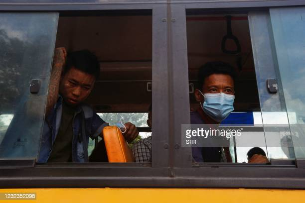 Newly released prisoners look on from a bus outside Insein Prison in Yangon on April 17 as thousands of inmates were freed nationwide to mark the...