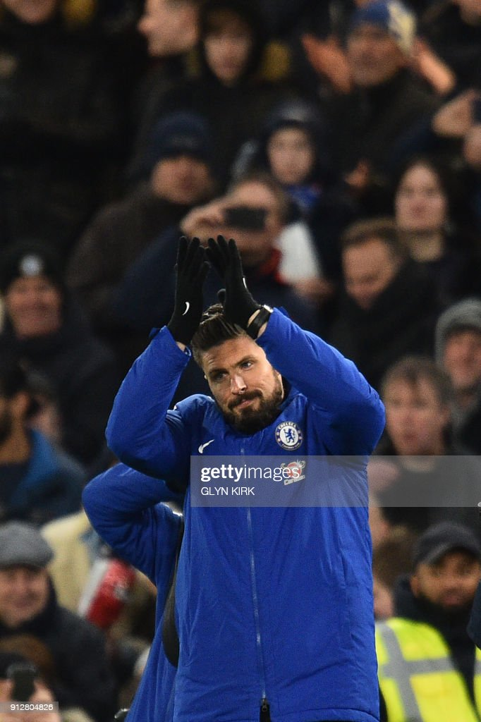 Newly signed Chelsea striker Olivier Giroud gestures to fans during the English Premier League football match between Chelsea and Bournemouth at Stamford Bridge in London on January 31, 2018. / AFP PHOTO / Glyn KIRK / RESTRICTED TO EDITORIAL USE. No use with unauthorized audio, video, data, fixture lists, club/league logos or 'live' services. Online in-match use limited to 75 images, no video emulation. No use in betting, games or single club/league/player publications. /