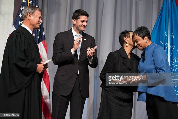 Newly sworn in Librarian of Congress Carla Hayden right gets a kiss from her mother Colleen as Speaker Paul Ryan RWis and Chief Justice John Roberts...