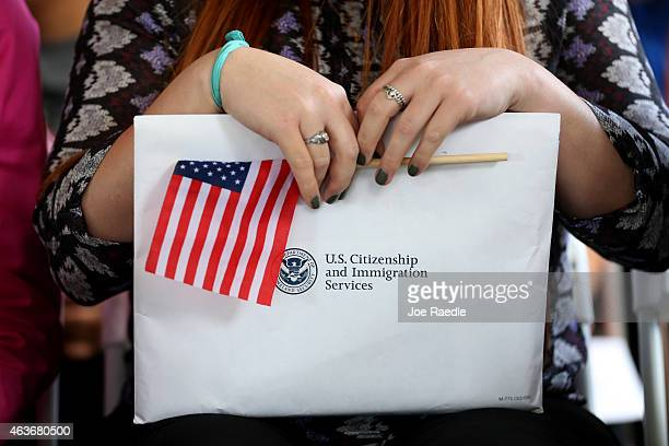 A newly sworn in United States citizen holds her paperwork during a naturalization ceremony put on by the US Citizenship and Immigration Services at...