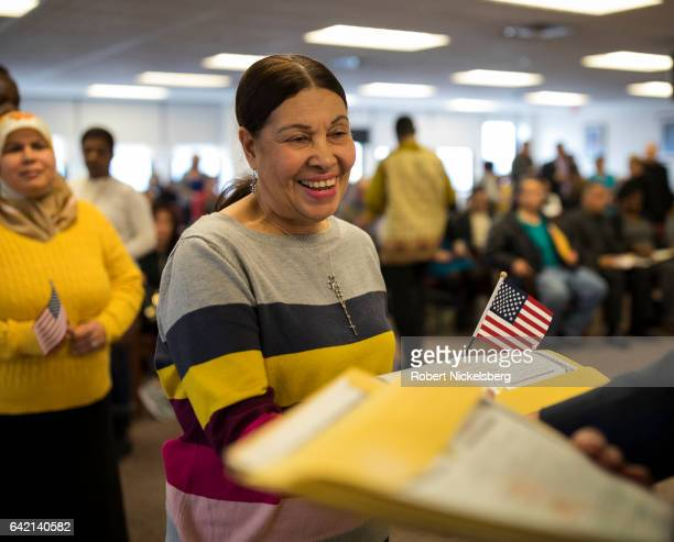 A newly sworn in US citizen center receives her Certificate of Naturalization from a US government employee right during a naturalization ceremony...
