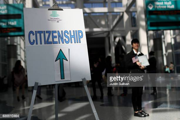A newly sworn in US citizen poses for a picture at the conclustion of a naturalization ceremony held by US Citizenship and Immigration Services at...