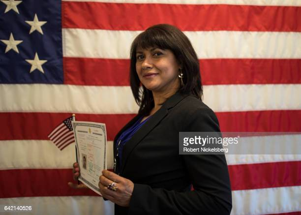 A newly sworn in US citizen stands for a picture holding her Certificate of Naturalization during a ceremony for new US citizens February 16 2017 in...