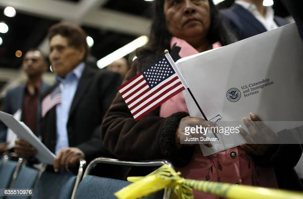 Newly sworn in US citizens wait in like to receive paperwork at the conclusion of a naturalization ceremony held by US Citizenship and Immigration...
