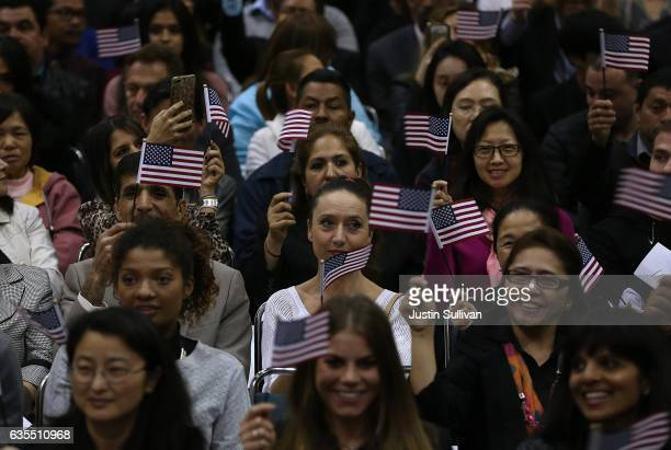 Newly sworn in US citizens wave American flags during a naturalization ceremony held by US Citizenship and Immigration Services at the Los Angeles...