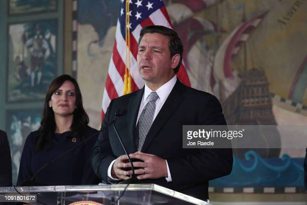 Newly swornin Gov Ron DeSantis speaks as his lieutenant governorJeanette Nuñez stands near him during an event at the Freedom Tower where he named...