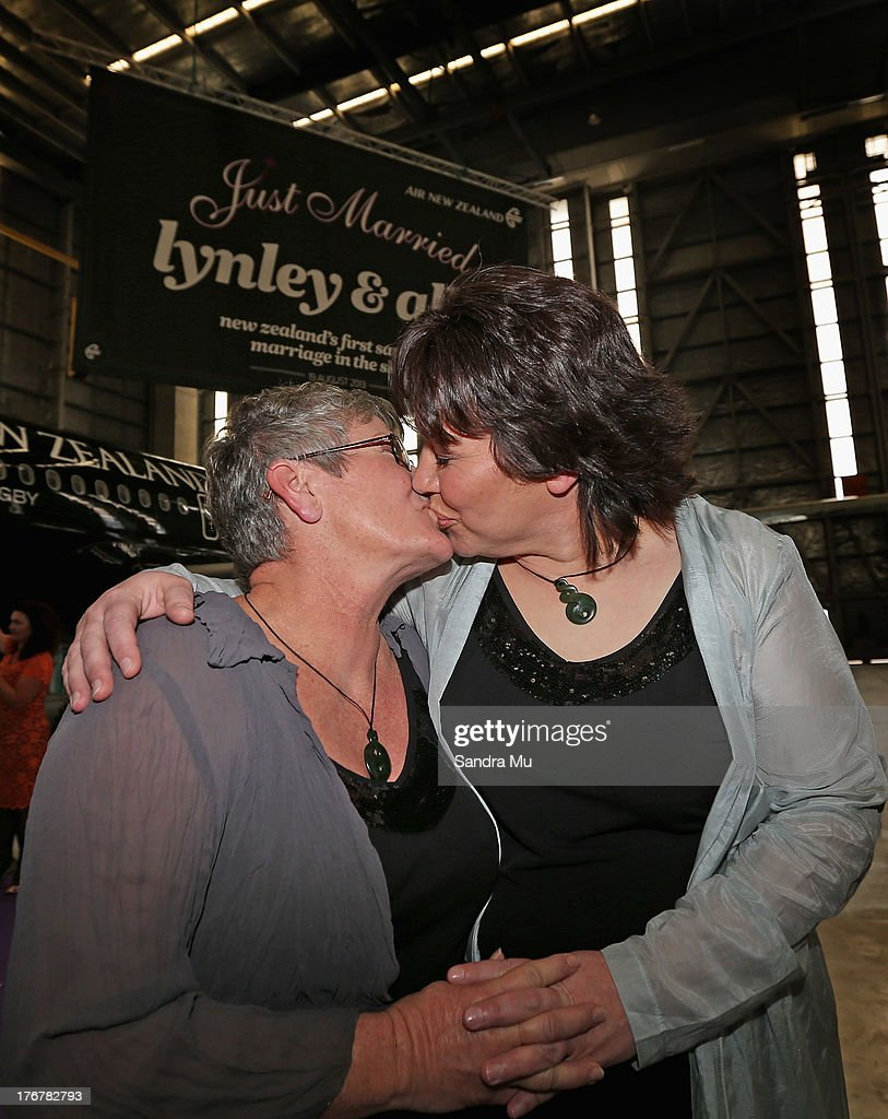 Newly wed couple Ally Wanikau (L) and Lynley Bendall share a kiss as they arrive at the reception inside the Air New Zealand hanger on August 19, 2013 in Auckland, New Zealand.
