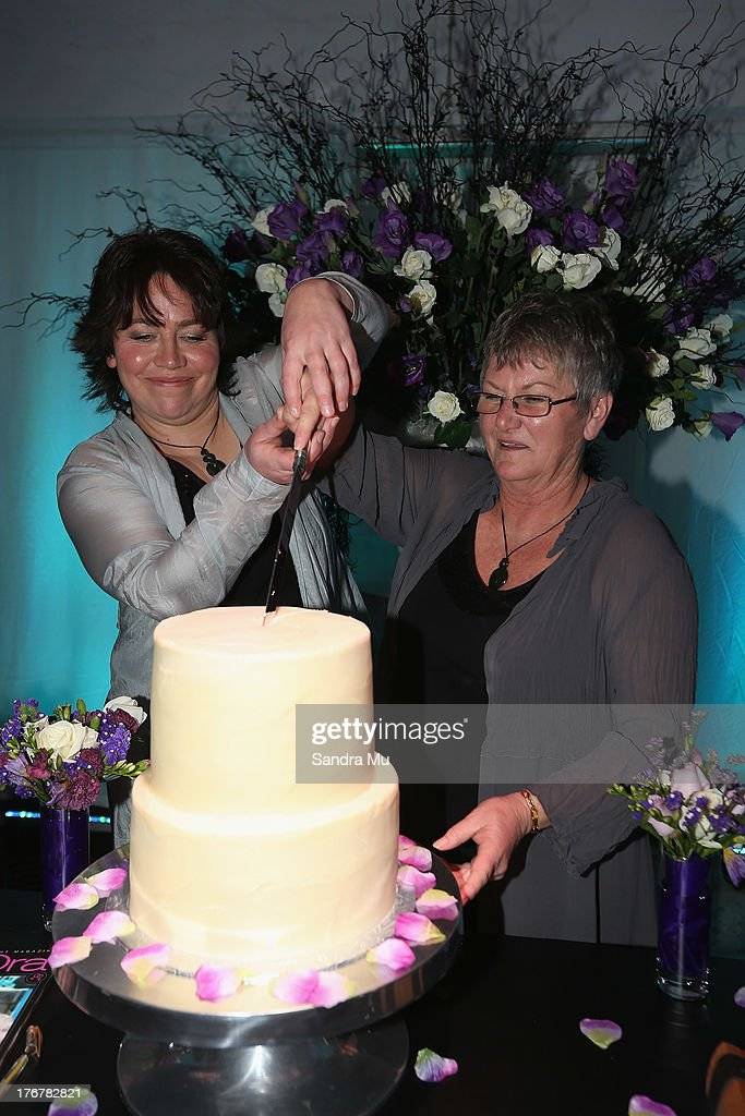 Newly wed couple Lynley Bendall (L) Ally Wanikau cut the cake during the reception inside the Air New Zealand hanger on August 19, 2013 in Auckland, New Zealand.