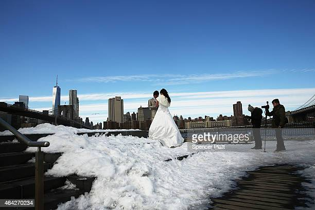 A newly wed couple poses for photographers near the East River on a cold day on February 23 2015 in New York City New York City and much of the East...
