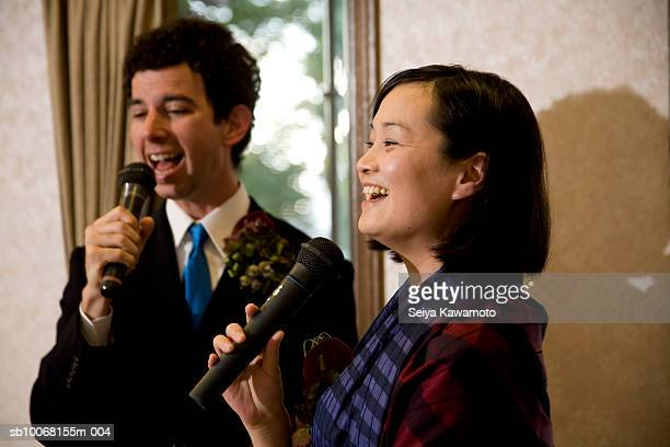 Newly wed couple singing to microphones at wedding party