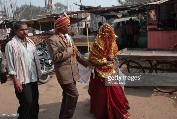 Newly wedding couple walk on street at Ganga River at Varanasi, Uttar Pradesh, India