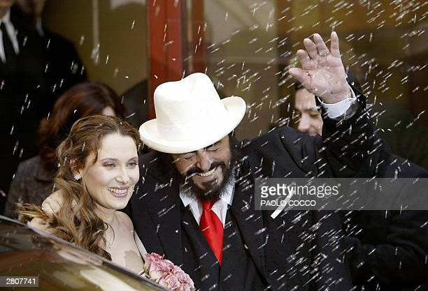 Newly weds Italy's famous tenor Luciano Pavarotti and Nicoletta Mantovani wave as people throw rice at them after a wedding ceremony in Modena's main...
