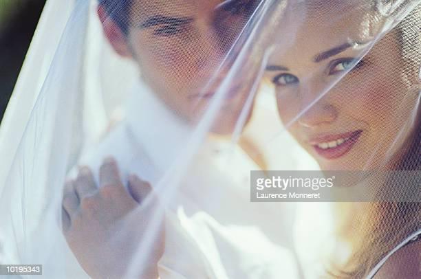 Newly weds under bride's veil, portrait, close-up