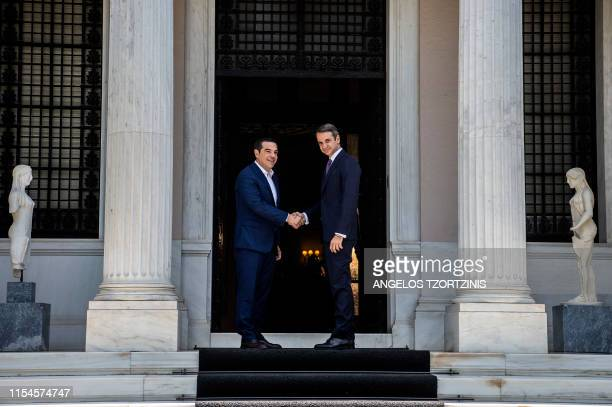 Newlyappointed Greek Prime Minister Kyriakos Mitsotakis shakes hands with former prime minister Alexis Tsipras at the Maximos Mansion in Athens on...