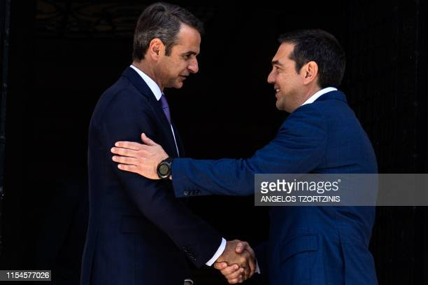 Newlyappointed Greek Prime Minister Kyriakos Mitsotakis shakes hands with outgoing Prime Minister Alexis Tsipras after their meeting at the Maximos...