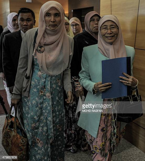 Newlyappointed Malaysian opposition leader Wan Azizah the wife of jailed Anwar Ibrahim walks with her daughter Nurul Izzah as they arrive for a press...