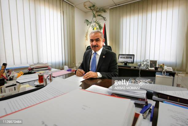 Newly-appointed Palestinian Prime Minister Mohammad Shtayyeh signs documents at his office in the West Bank city of Ramallah on March 10, 2019. -...