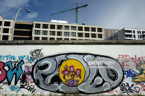 Newlybuilt office buildings are seen behind a portion of the socalled East Side Gallery a 13 kmlong stretch of the Berlin wall in Berlin on September...