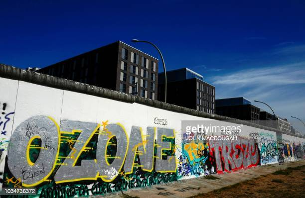 Newly-built office buildings are seen behind a portion of the so-called East Side Gallery, a 1,3 km-long stretch of the Berlin wall, in Berlin on...