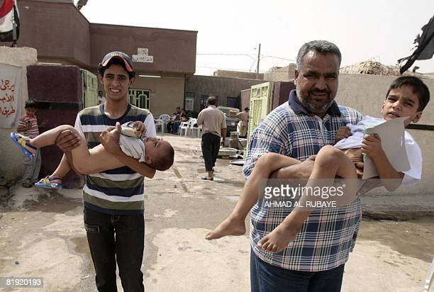 Newlycircumcised Iraqi boys are carried out from a clinic following a mass circumcision in Baghdad's Sadr City on July 13 2008 Around 700 boys were...