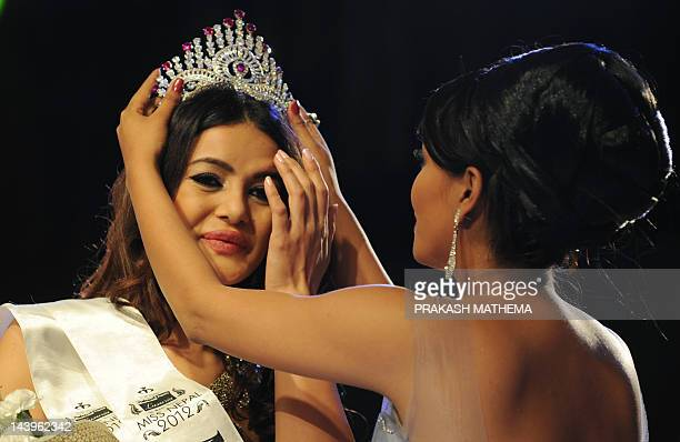 Newlycrowned Miss Nepal Shristi Shrestha has her crown fitted by former Miss Nepal Malina Joshi following the contest in Kathmandu on May06 2012 Miss...