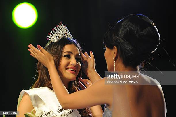 Newlycrowned Miss Nepal Shristi Shrestha has her crown fitted by former Miss Nepal Malina Joshi following the contest in Kathmandu on May 6 2012 Miss...