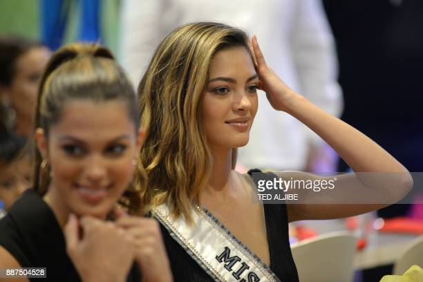 Newlycrowned Miss Universe DemiLeigh NelPeters of South Africa arranges her hair next to Miss Universe 2016 Iris Mittenaere of France during a visit...