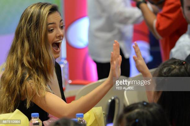 Newlycrowned Miss Universe DemiLeigh NelPeters of South Africa makes a highfive with a child from an orphanage during a visit to a popular fast food...