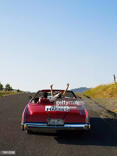 Newlyeds driving down rural road in convertible with 'Just Married' sign, arms raised