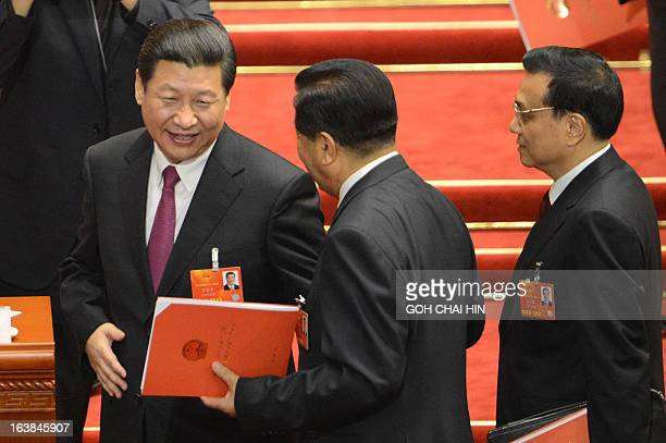 Newlyelected Chinese President Xi Jinping talks to chairman of the NPC Liu Yunshan while newlyelected Premier Li Keqiang follows after the closing...