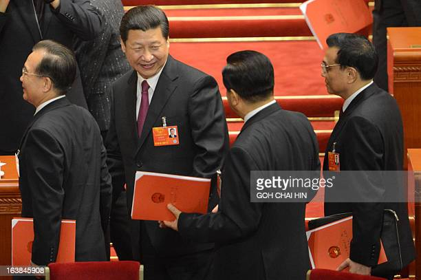 Newlyelected Chinese President Xi Jinping talks to chairman of the NPC Liu Yunshan after the closing session of the National People's Congress at the...