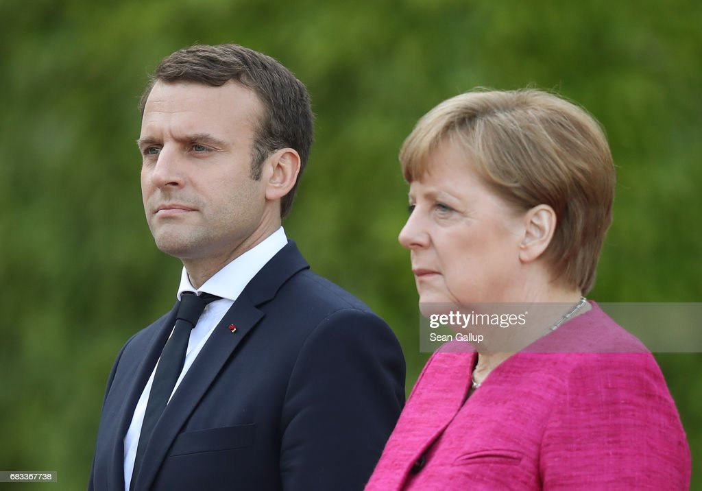 Newly-elected French President Emmanuel Macron and German Chancellor Angela Merkel listen to their nations' respective national anthems upon Macron's arrival at the Chancellery on May 15, 2017 in Berlin, Germany. Macron is visiting Berlin only a day after being sworn in as president in Paris. While Macron and Merkel have both demonstrated an unwavering commitment to the European Union and Merkel strongly applauded Macron's election, they are likely to differ over Macron's desire for E.U.-issued bonds, a measure Merkel has strongly opposed in the past.