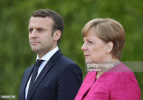 Newly-elected French President Emmanuel Macron and German Chancellor Angela Merkel listen to their nations' respective national anthems upon Macron's...