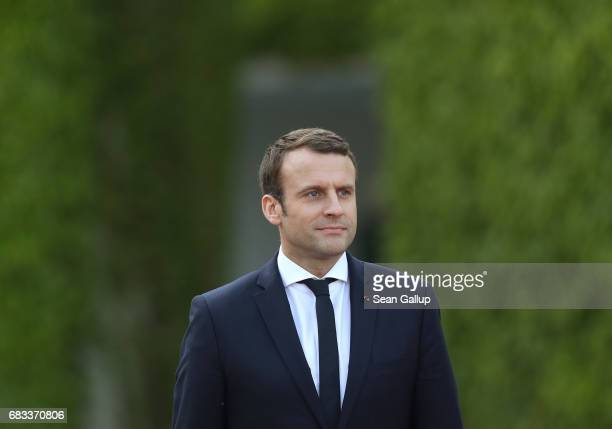 Newly-elected French President Emmanuel Macron and German Chancellor Angela Merkel walk to review a guard of honour upon Macron's arrival at the...